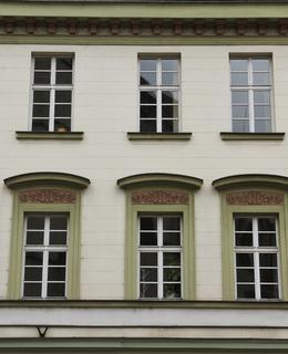 Okna se segmentově ukončenou šambránou v 1. patře a nasedající na jednotlivé parapetní římsy.ve 2. patře, omítka s bosáží (Foto M. Polák, 2021)